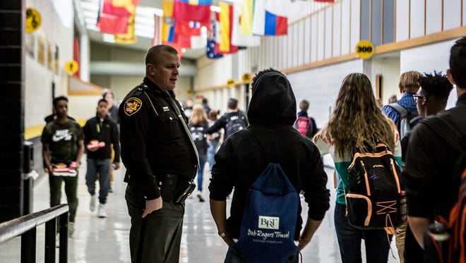 Deputy Marc Brill talks with students at Watkins Memorial high School between classes on Thursday March, 22. Southwest Licking Schools hired Brill as a school resource officer. Since his start date, March 5, Brill has been getting to know the students at all Southwest Licking Schools and has given a number of presentations to classes.