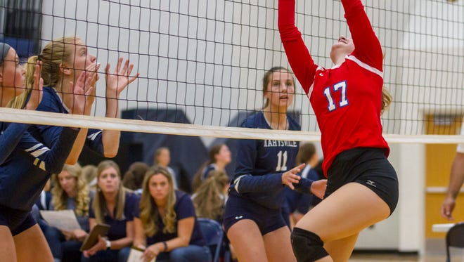 St. Clair's Elena Cousino sets the ball over the net during their game against Marysville Sept. 7.