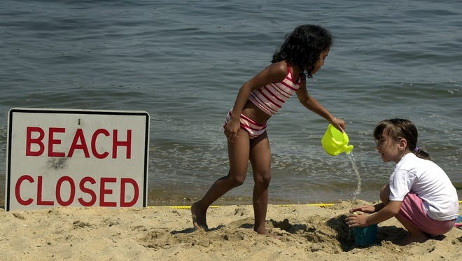 Children play with water from the water fountain on the beach at Hudson Park in New Rochelle.