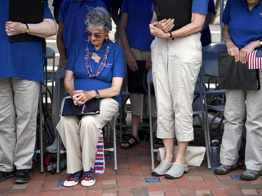 Virginia G. Bailey, of Weaverville, prays alongside her fellow The Reuter Center Singers Monday May 29, 2017 during the Memorial Day Concert and Ceremony in Pack Square Park.