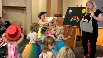 Mari Redington, children's library assistant, tells a story about rainbows during Drag Storytime at the Iowa City Public Library.