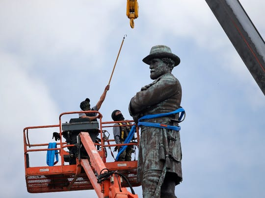 In this May 19, file photo, workers prepare to take down the statue of former Confederate general Robert E. Lee, which stands over 100 feet tall, in Lee Circle in New Orleans.