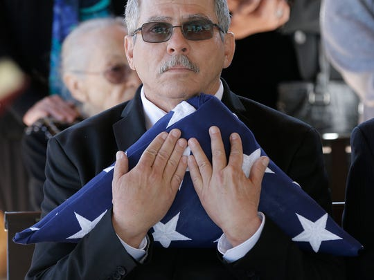 Mark Torres holds the flag honoring his father, World War II veteran Dr. Joseph E. Torres, during a graveside service Friday at Fort Bliss National Cemetery.