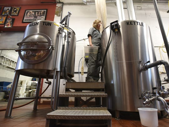 Lori Wince watches the progress of a beer brewing in