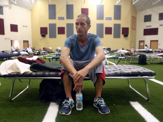 Kevin Sweet from Corpus Christi sits in his cot after