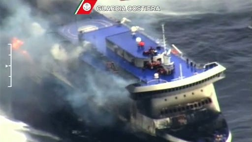 In this image taken from a video released by the Italian Coast Guard, smoke billows from the Italian-flagged Norman Atlantic that caught fire in the Adriatic Sea, Sunday, Dec. 28, 2014. Italian and Greek rescue crews battled gale-force winds and massive waves as they struggled Sunday to evacuate hundreds of people from a ferry on fire and adrift in the channel between Italy and Albania. At least one person died and two were injured. The fire broke out before dawn Sunday on a car deck of the Italian-flagged Norman Atlantic, traveling from the western Greek port of Patras to the Italian port of Ancona on the Adriatic, with 422 passengers and 56 crew members on board. (AP Photo/Italian Coast Guard)
