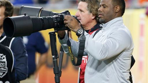 Former MLB baseball player Ken Griffey Jr. shoots pictures from the sidelines during the first half of the Fiesta Bowl NCAA college football game between Arizona and Boise State, Dec. 31 in Glendale, Ariz.