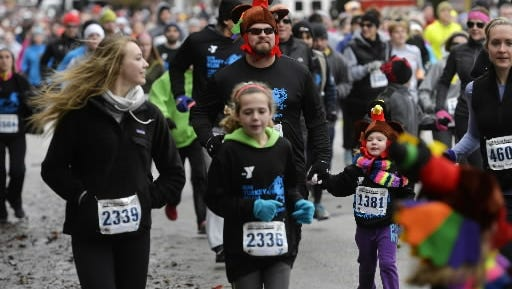 Joe Stover of Springettsbury Township holds his 5-year-old daughter Emily's hand as they wear turkey hats and run together in the YMCA of York County's 18th annual Turkey Trot 5K on Thursday, Nov. 27, 2014.