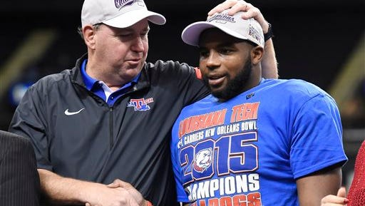Louisiana Tech coach Skip Holtz congratulates running back Kenneth Dixon, right, on receiving the MVP award following the New Orleans Bowl against Arkansas State on Saturday.