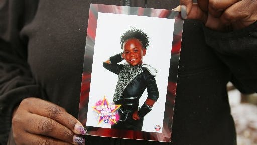 An aunt holds a photo of 7-year-old Chanell Berry, who was fatally shot Sunday.