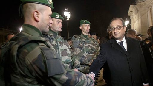 "France's President Francois Hollande, right, shakes hands with a foreign legionnaire as he visits the security measures at the Champs Elysees in Paris, Thursday, Dec 31, 2015. French President Francois Hollande has told the nation that the terrorist threat is still at its ""highest level.""In his traditional New Year's Eve speech, Hollande said: ""We just lived a terrible year."" (Michel Euler - The Associated Press)"