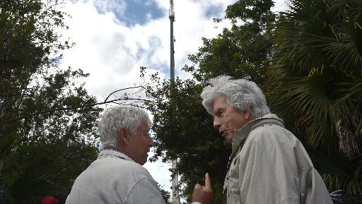Sandy Kasten (right), a John's Island neighborhood resident, talks with Jerry Weick (left) Vice Mayor of Indian River Shores, after a 115-foot crane was brought into Indian Roiver Shores in February to show what a 115-foot cell tower would look like. The Town Council on Monday approved a lease for the tower on town property.