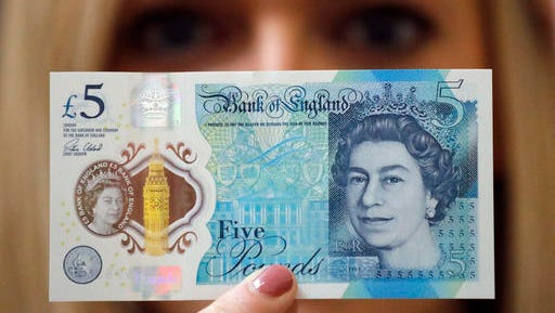 FILE - In this Tuesday, Sept. 6, 2016 file photo, a Bank of England employee shows the new five pound note at the Bank of England Museum in London. The new plastic 5-pound note is stronger, cleaner and safer, but vegans and vegetarians are calling for the new bank notes, which have only been in circulation for two months, to be replaced because they are made with a substance derived from animal fat.