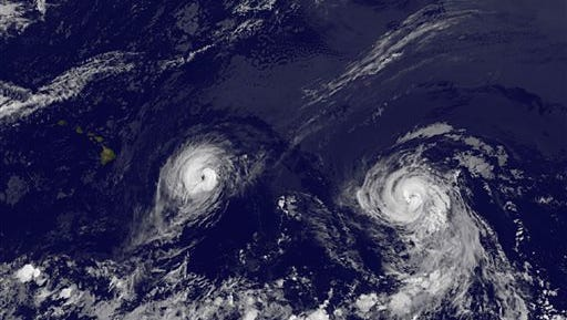 This image provided by NOAA taken Thursday Aug. 7, 2014 at 2 a.m. EDT shows Hurricane Iselle, left and Hurricane Julio. Iselle was supposed to weaken as it slowly trudged west across the Pacific. It didn't _ and now Hawaii is poised to take its first direct hurricane hit in 22 years. The center of Hurricane Iselle is expected to pass very near or over the Big Island Thursday night and just south of the smaller islands Friday. Some weakening is forecast during the next 48 hours however Iselle is still expected to be near hurricane strength as it impacts the Big Island. (AP Photo/NOAA)