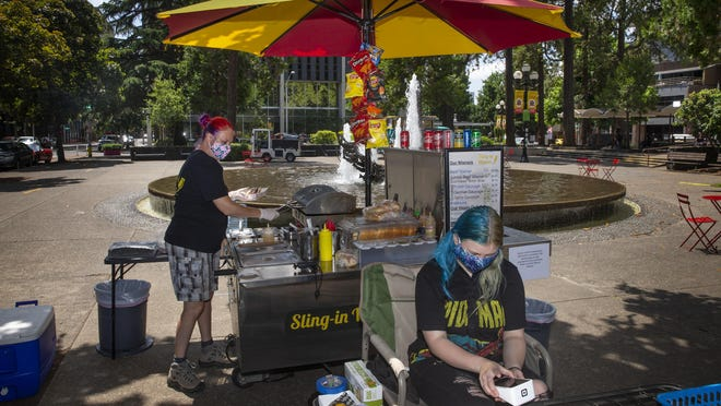 Misti Hagan, left, and her daughter, Rhain Hagan, 15, sell hot dogs from their food stand Sling-in Wiener at the Park Blocks in Eugene. [Chris Pietsch/The Register-Guard] - registerguard.com