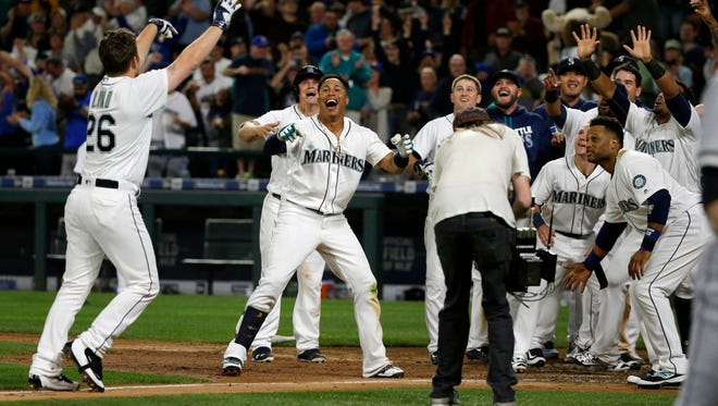 Seattle Mariners' Adam Lind, left, is greeted at home plate by teammates after he hit a three-run walk-off home run in the ninth inning of a baseball game against the Chicago White Sox, Monday, July 18, 2016, in Seattle. The Mariners beat the White Sox 4-3.