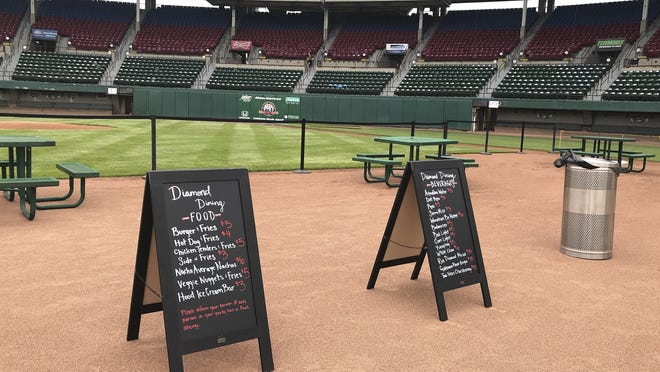 Menu boards and tables occupied the third base infield dirt in preparation for dining guests at McCoy Stadium, home of the Pawtucket Red Sox, in Pawtucket, Rhode Island, on May 27, 2020. With the Minor League Baseball season canceled, the Red Sox sent their top prospects to Pawtucket for Summer Camp.