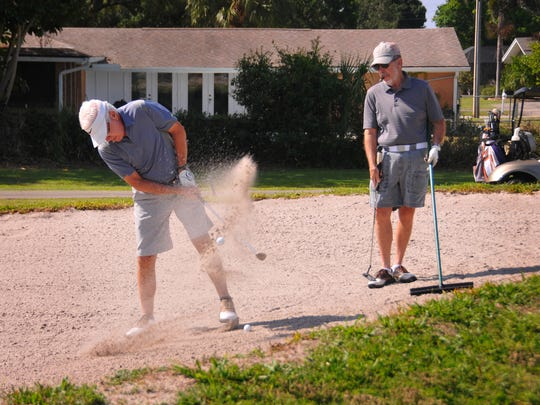 George Edwards blasts out of the sand trap while Dale Henry waits his turn Tuesday morning at the Mallards Landing Golf Course, owned by the city of Melbourne.