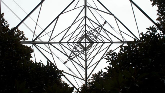 TVA transmission tower rises above a grove of magnolia trees inside The Centre at Deane Hill shopping complex.