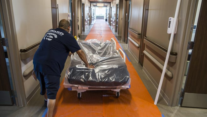 A worker is shown last year moving a bed into a room at Baylor Scott & White Medical Center in Buda. Some patients on Medicaid defer routine health care and opt instead for costly visits to the emergency room.