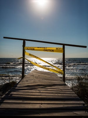 Caution tape blocks the end of a dune walkover at a vacation rental in Cape San Blas in October 2015 after a strong storm caused a significant amount of erosion damage to the critically eroded beach.