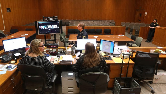 Judge Maija C. Dixon handling arraignments in Rochester City Court virtually from her home using Skype to connect with attorneys and with  defendants in the Monroe County Jail.  The people in the courtroom are clerks Kendra Dundon, left, and Katie Ellis along with deputies Joseph Imbergamo and Julie VanDerMar.