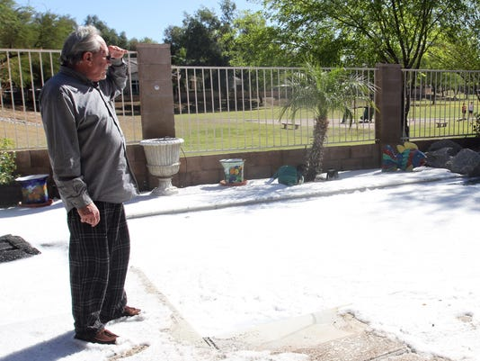 Doug Goetsch takes a look at his backyard in Gilbert that was sprayed with fire suppression foam by firefighters when they battled a blaze across the street Saturday evening.