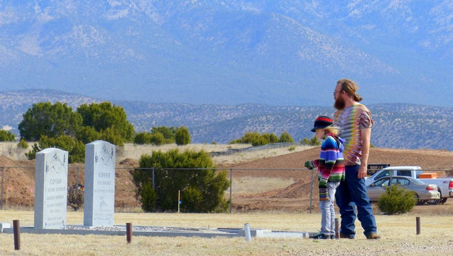 Two visitors to Fort Stanton Merchant Marine and Military Cemtery pay their respects to a former ship's captain who championed the cause of the cemetery. It recently was selected as the first of four new state veterans cemeteries to be developed in New Mexico.