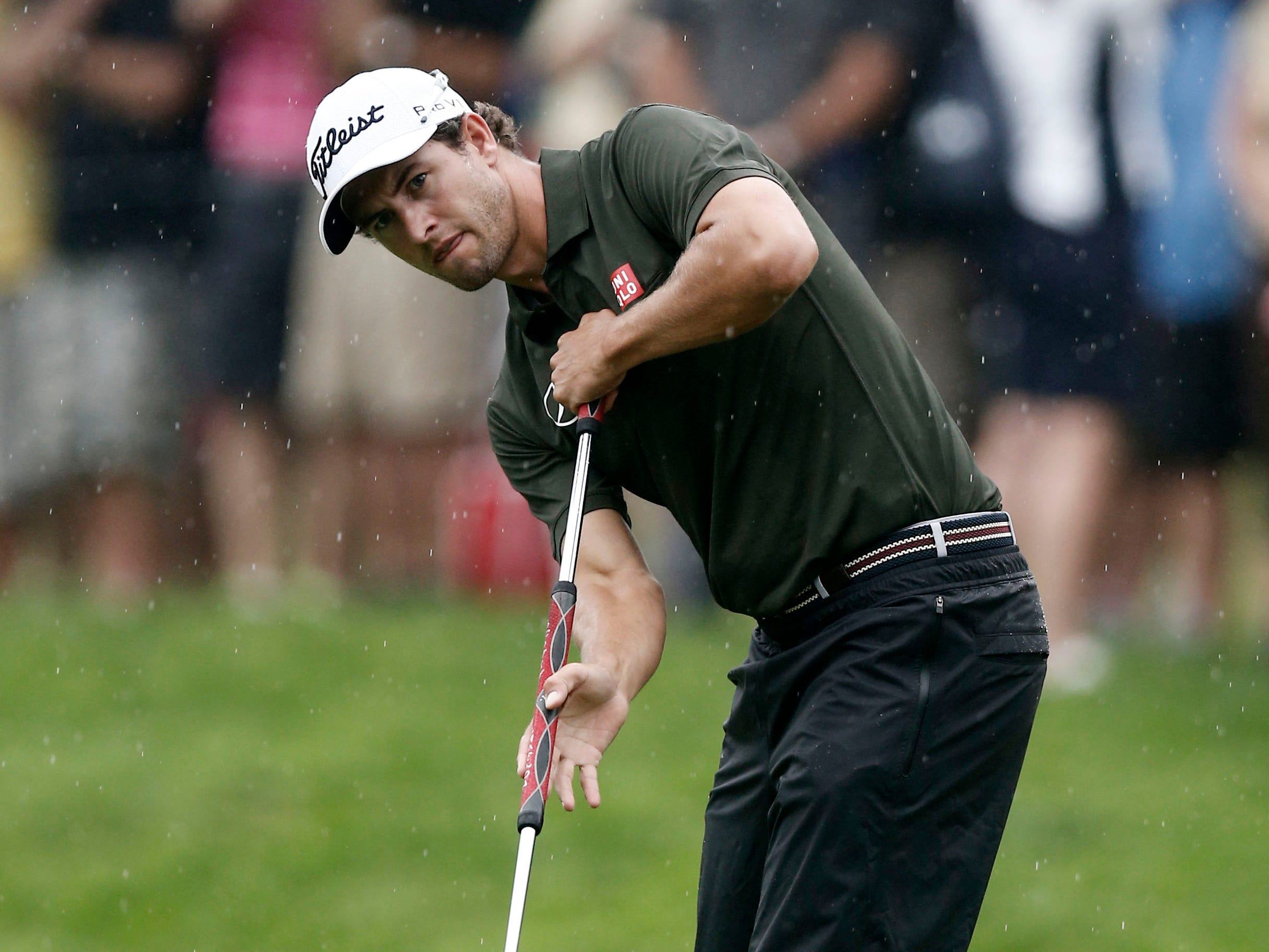 Adam Scott eyes his putt on the 11th green.