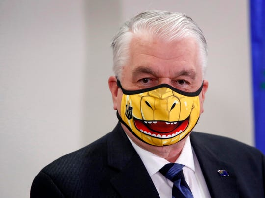 Nevada Gov. Steve Sisolak speaks wearing a face mask themed after the Vegas Golden Knights' mascot Chance the Golden Gila Monster during a news conference in Las Vegas.