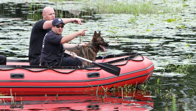 """Connecticut state trooper Chris Porrini and his K9 partner """"Unit"""" along with Danbury firefighter Jamie Gagliardo use a Danbury fire department boat as they search for a suspect that led police on a two state chase before finally crashing his vehicle on Route 7 in Danbury, CT. July 4, 2015. The suspect had handcuffs on one hand and was in the process of being arrested when he escaped leading police on a chase from Connecticut into Putnam County and back into Connecticut where he crashed."""