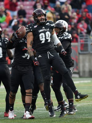 Louisville's James Hearns (99) celebrates after causing a fumble recovered by Louisville's Trevon Young as the Cardinals take on Virginia on Saturday at Papa John's Cardinal Stadium. Nov. 11, 2017