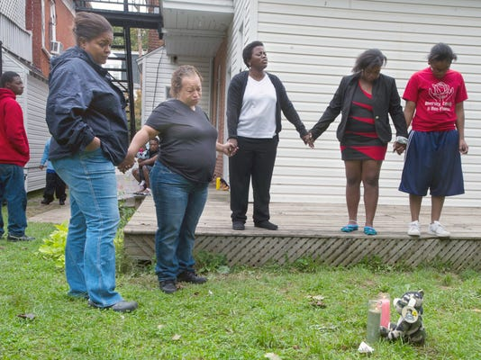 A group gathers to pray near a memorial that was placed in the yard in the 100 block of West Jackson Street in York where Denzel Turane, age 18, was found mortally wounded and then later died and girl in the kitchen with a wound to her arm. Several bullet casings in the dining room. Sunday October 7, 2012. YORK DAILY RECORD/SUNDAY NEWS - PAUL KUEHNEL