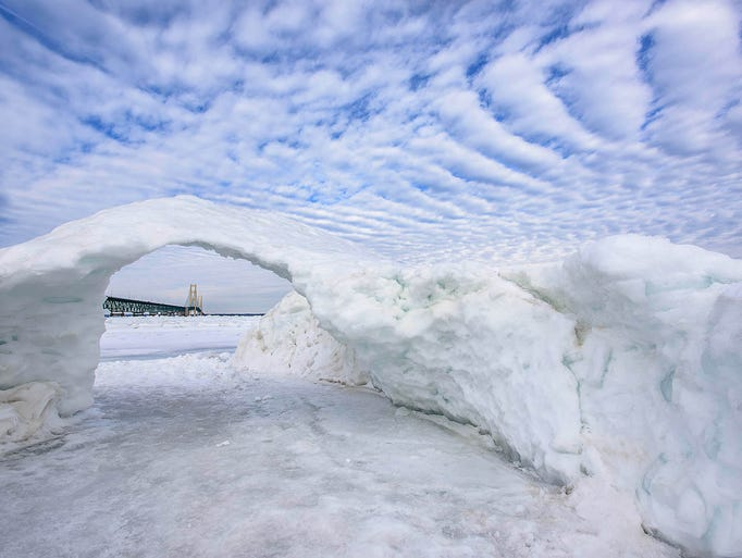 The Mackinac Bridge is seen through a snow arch on