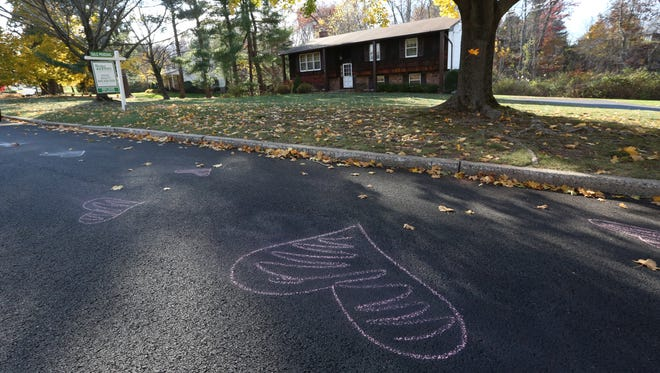 A neighbor painted over and drew chalk hearts to cover graffiti painted on her street.