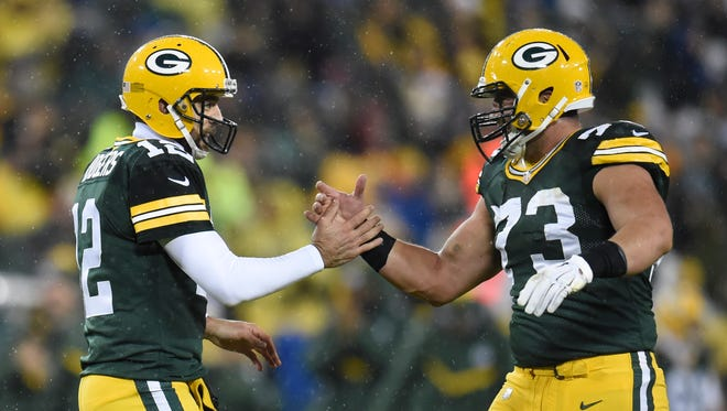 Green Bay Packers quarterback Aaron Rodgers (12) and center JC Tretter (73) celebrate on the field in the first quarter against the Chicago Bears at Lambeau Field.