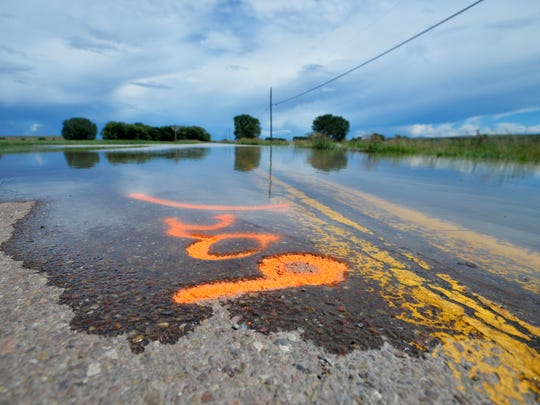 Quickly rising floodwater from the Sun River covers a spray paint marker on South Manchester Road on Thursday afternoon.  Cascade County officials used spray paint to note the time and level of floodwater on the road.