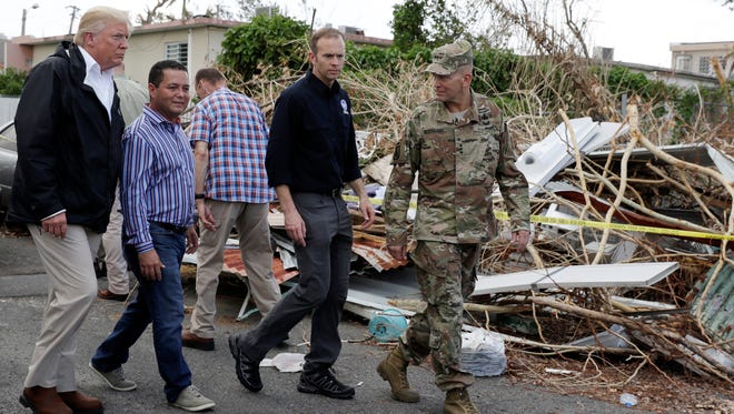 President Trump walks with FEMA administrator Brock Long, second from right, and Lt. Gen. Jeff Buchanan, right as he tours an area affected by Hurricane Maria in Guaynabo, Puerto Rico, on Oct. 3, 2017.