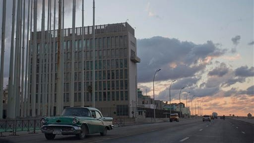 This Dec. 17 file photo shows a classic American car driving past the U.S. Interests Section building in Havana, Cuba. A half-century after Washington severed relations with Cuba, the seven-story mission is set to become a full-fledged embassy. The U.S. and Cuba announced on Dec. 17 they are re-establishing full diplomatic relations.