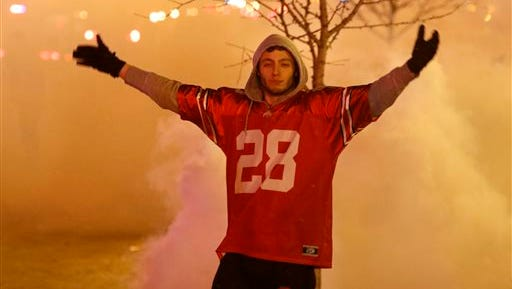 An Ohio State fan stands in a cloud of tear gas as police officers try to disperse a crowd of Ohio State fans trying to block High Street in Columbus, Ohio, during their celebration following the Buckeye's 42-20 win over Oregon at the National Championship football game between Ohio State and Oregon on the campus of Ohio State University in Columbus, Ohio,  Monday, Jan. 12, 2015. (AP Photo/Paul Vernon)