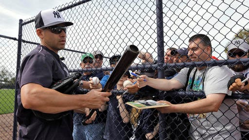 New York Yankees' Jacoby Ellsbury looks at a bat while signing autographs before a spring training baseball game against the Philadelphia Phillies Thursday, March 3, 2016, in Tampa, Fla. (AP Photo/Chris O'Meara)