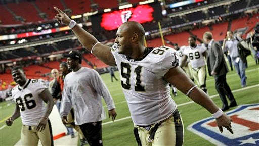 In this Dec. 27, 2010, file photo, New Orleans Saints defensive end Will Smith (91) celebrates a 17-14 win over the Atlanta Falcons in an NFL football game in Atlanta. Smith was fatally shot after a traffic accident in New Orleans.
