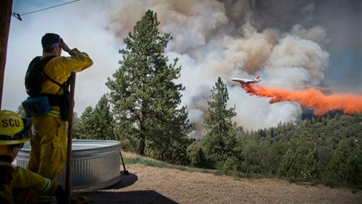 A DC-10 Air Tanker makes a drop on the Sand Fire at the middle fork of the Cosumnes River in Northern California as firefighters standby to protect a home on Saturday, July 26, 2014. Hundreds of firefighters are working in rugged terrain and triple-digit temperatures.
