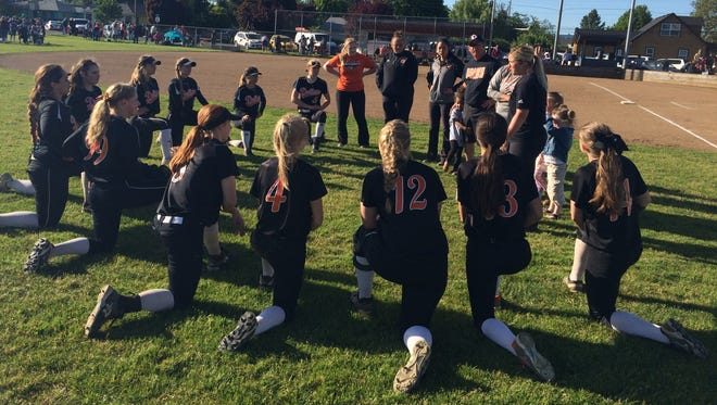 Dallas softball coach Brandi Jackson talks to her team after they beat Parkrose 7-0 on Wednesday in the Class 5A state playoffs.