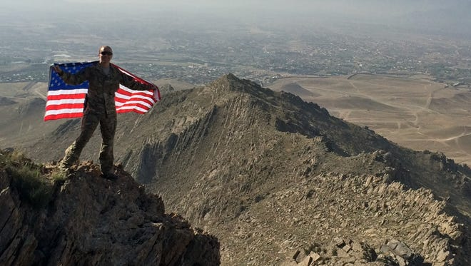 Leigh Ann Hester stands with the American flag while hiking the Gharib Ghar, just outside Kabul, Afghanistan, in 2015.
