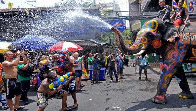 Foreign tourists spray an elephant with water guns as it spouts water during the Songkran festival to mark the Thai new year along the tourist area of Khao San road in Bangkok on April 12, 2010.