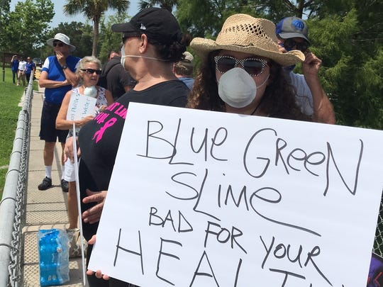 Katelyn Collier, a sophomore at Cypress Lake High School, came to the Franklin lock and dam on the Caloosahatchee River on Sunday to protest conditions that have led to the formation of blue-green algae.