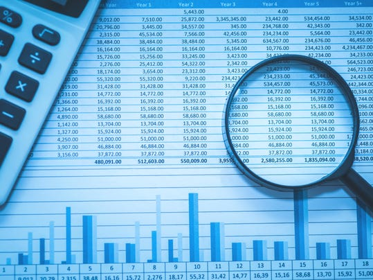Spreadsheet bank accounts accounting with calculator and magnifying glass.