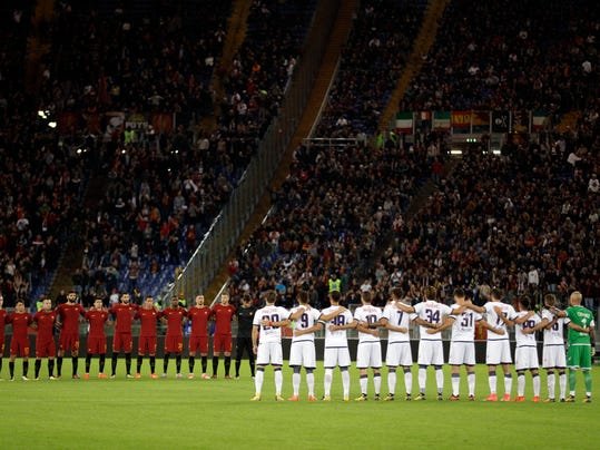 """FILE - In this Wednesday, Oct. 25, 2017 file photo, players observe a minute of silence prior to the start of a Serie A soccer match between Roma and Crotone, at Rome's Olympic Stadium. The Italian football federation has called up Lazio to a hearing following the shocking scenes of anti-Semitism from the Serie A club's supporters last month. After their team's victory over Cagliari on Oct. 22, Lazio fans littered the Stadio Olimpico in Rome with images of Anne Frank, the young diarist who died in the Holocaust, wearing a jersey of city rival Roma. The FIGC says there was a """"clear anti-Semitic intent"""" and that it """"constituted discriminatory behavior.""""  (AP Photo/Andrew Medichini, File)"""