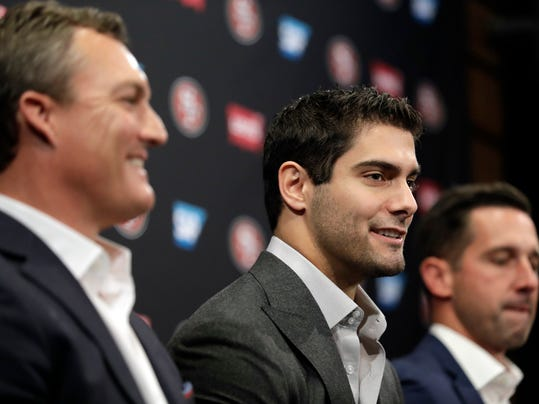 San Francisco 49ers quarterback Jimmy Garoppolo, center, fields questions alongside general manager John Lynch, left, and head coach Kyle Shanahan during an NFL football press conference Friday, Feb. 9, 2018, in Santa Clara, Calif. Garoppolo has signed a five-year contract with the 49ers worth a record-breaking $137.5 million. (AP Photo/Marcio Jose Sanchez)